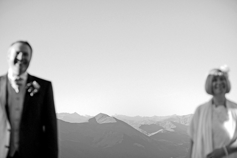 bride and groom standing apart with mountains in focus in background