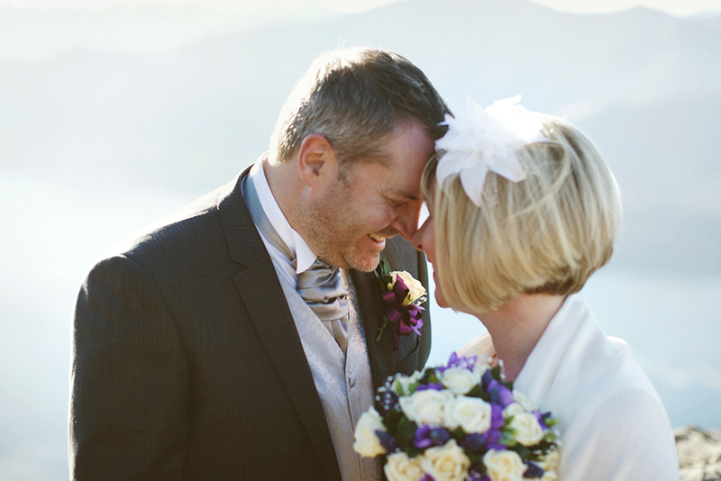close up of groom and bride touching foreheads on ledge