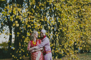 couple cuddling in front of autumn trees