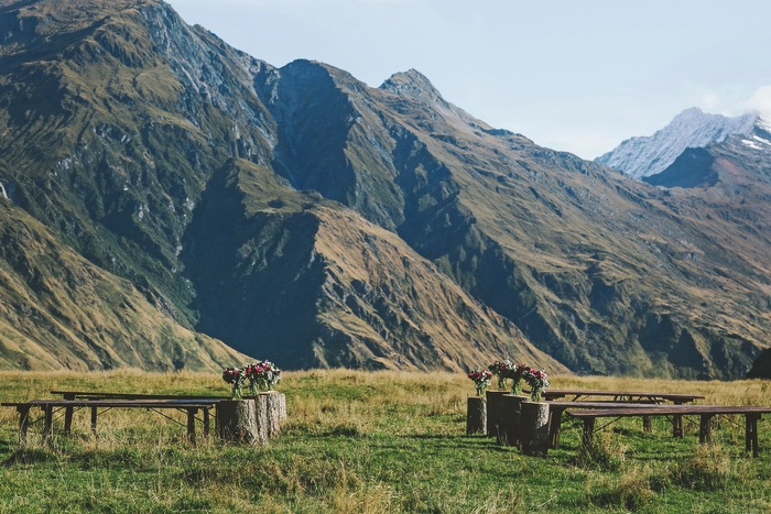 Ceremony Site, with bench seats and tree stumps with flowers in jars on them at outdoor wedding ceremony Mt Aspiring National Park, New Zealand