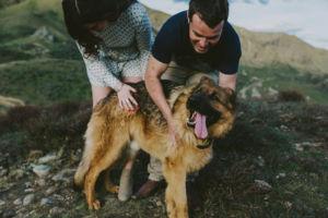 couple cuddling their dog on a mountaintop kurow