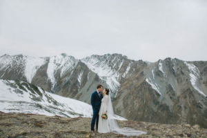 bride and groom on glacier with snowy mountain behind them
