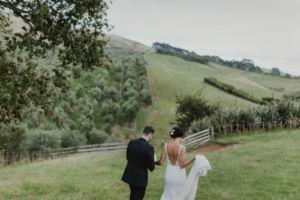 bride and groom walking towards green hills