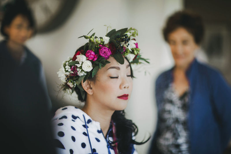 bride in flower crown having make up done