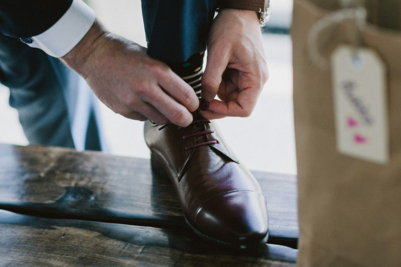 close up of groom doing up shoe
