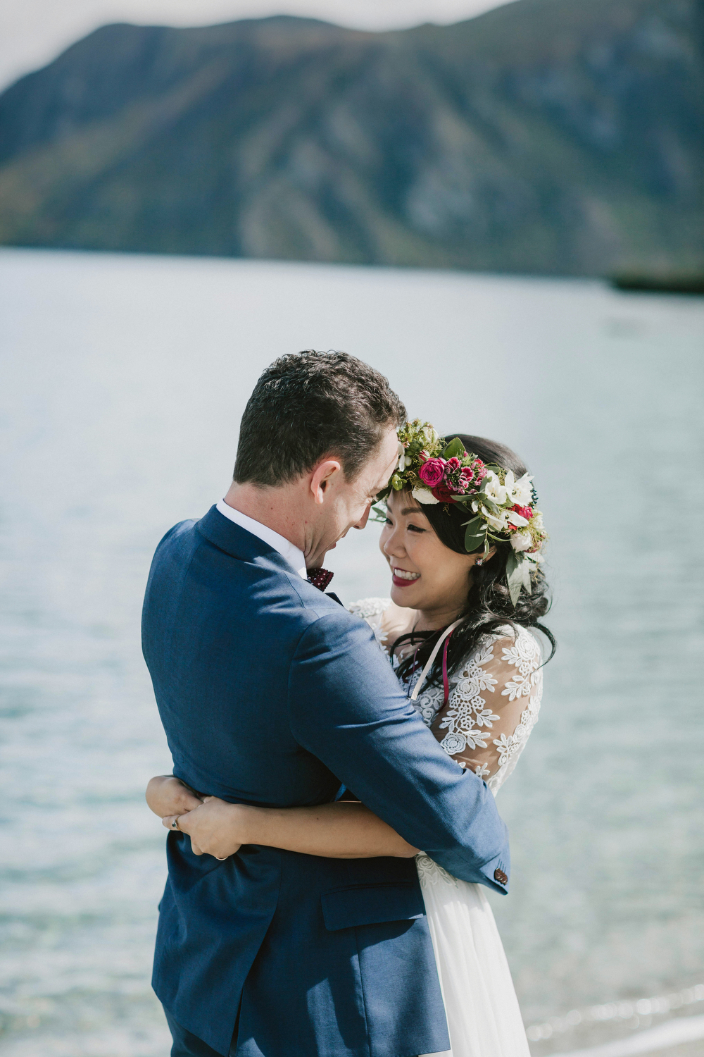 close up of bride and groom facing each other in front of lake