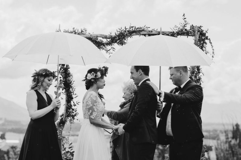 bride and groom under umbrellas b&w