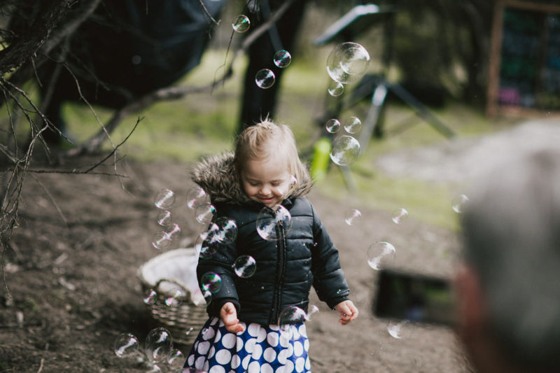 cute little girl playing with bubbles