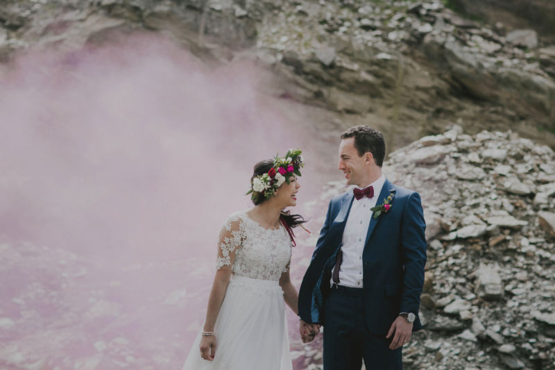close up of bride and groom surrounded by pink smoke