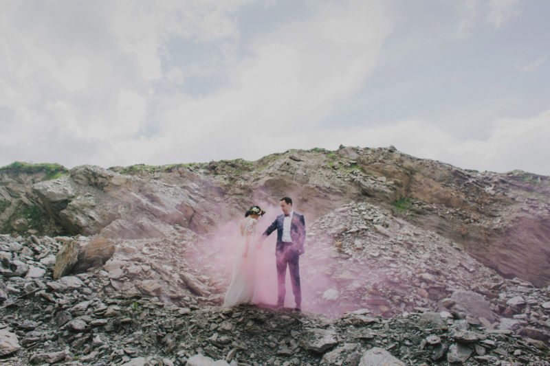 wide shot of bride and groom surrounded by pink smoke
