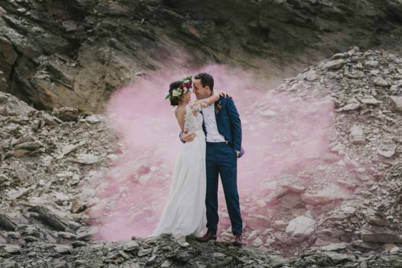 kissing bride and groom surrounded by pink smoke