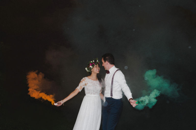 bride and groom with smoke bombs outside in the dark