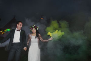 bride and groom running with smoke bombs in the dark