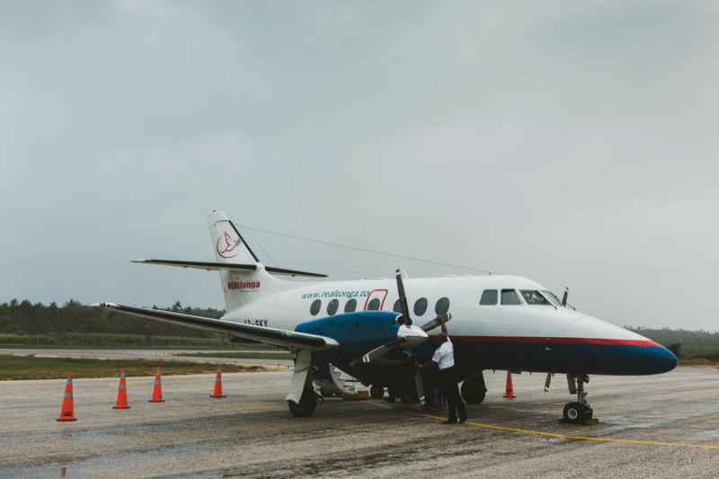 pilot tending small plane on runway