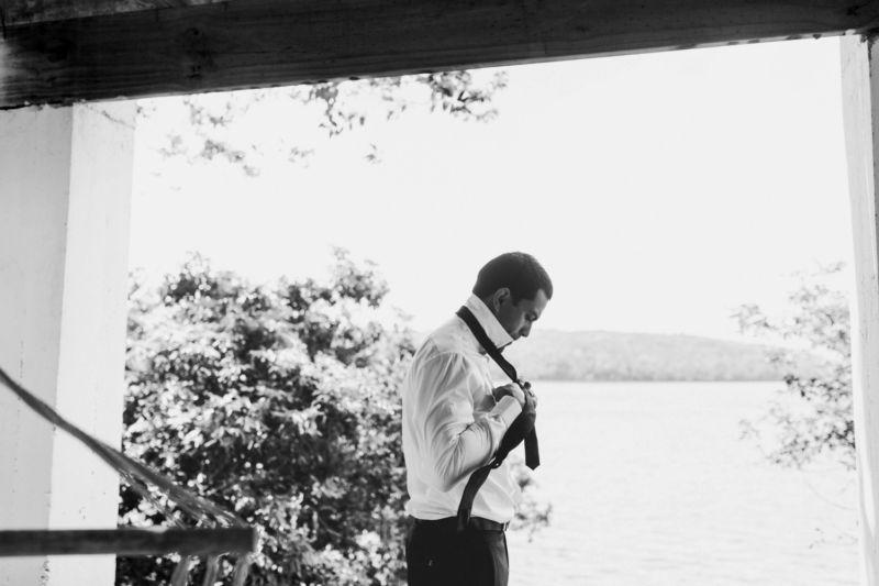 profile of groom doing tie against window