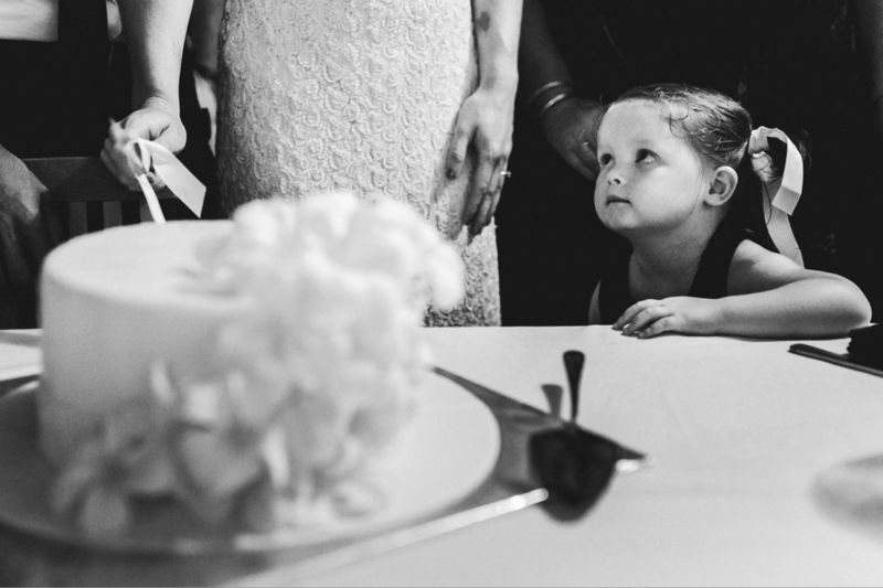flower girl looking at bride and cake cutting