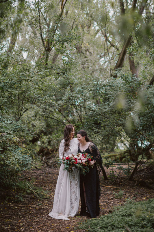 brides laughing together in forest