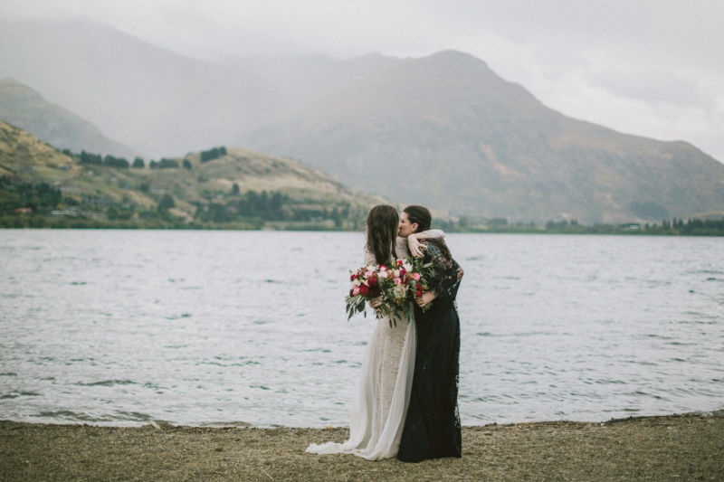 brides embracing in front of lake