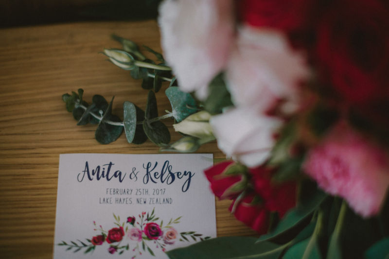 close up of invitation and flowers on table