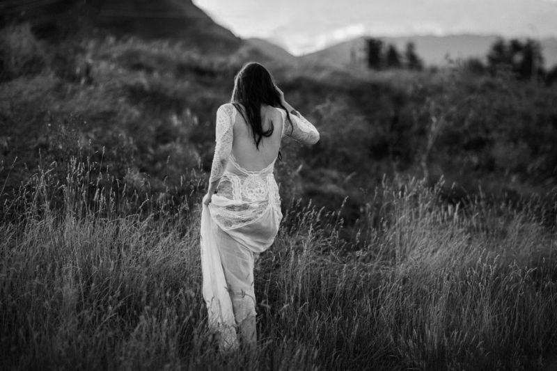 b&w of bride walking into long grass