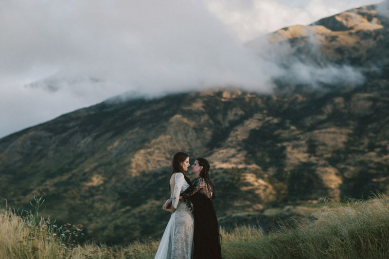 brides embracing with dramatic mountain behind them - facing each other