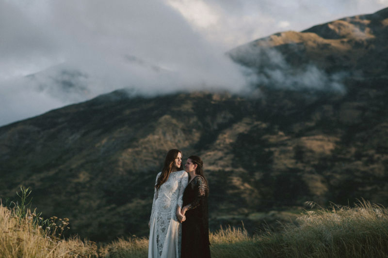 brides embracing with dramatic mountain behind them - spooning each other