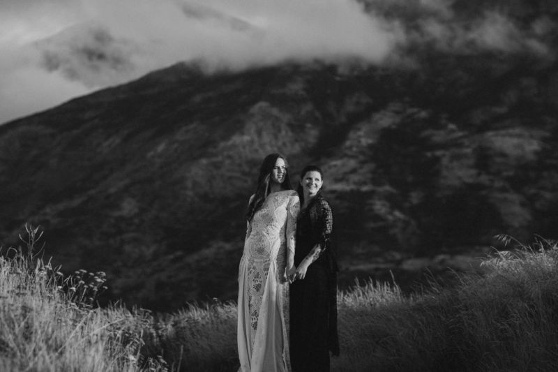 brides embracing with dramatic mountain behind them - spooning each other b&w