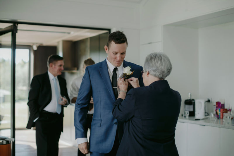 grooms flower being pinned on his jacket