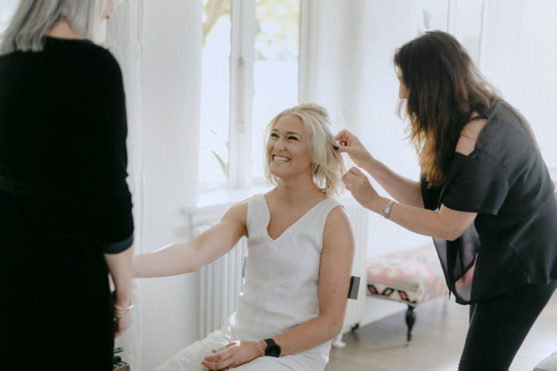 bride smiling while getting hair done