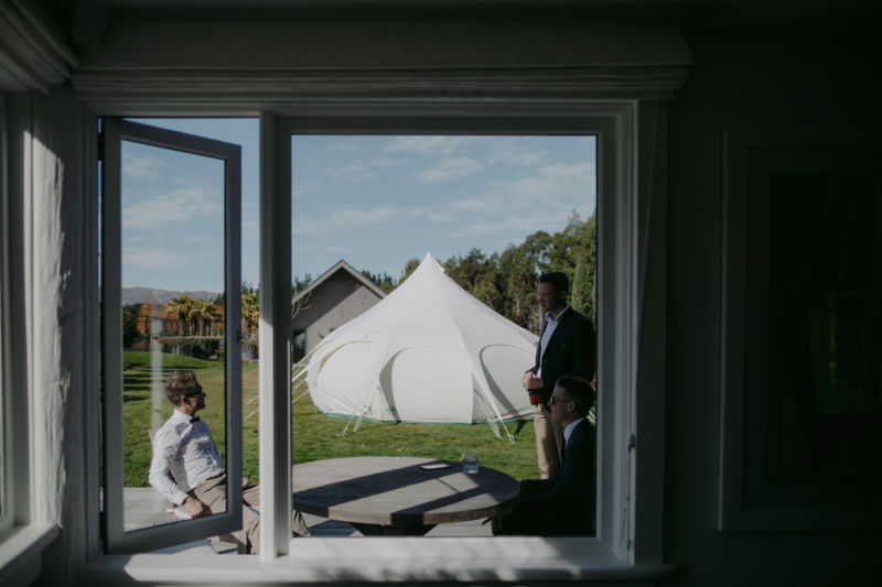 view of bell tents out of the window with guests standing chatting