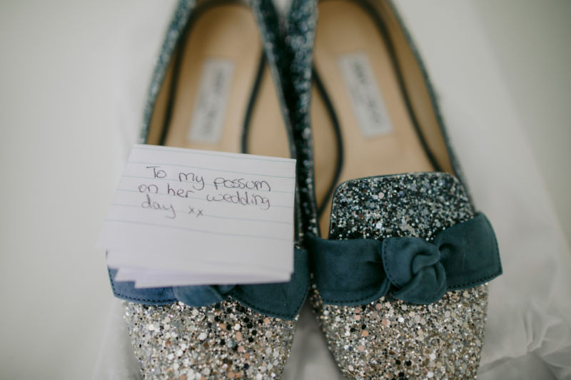 close up of brides sparkly shoes with a sweet note attached