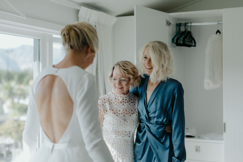 brides mother and sister admiring her dress