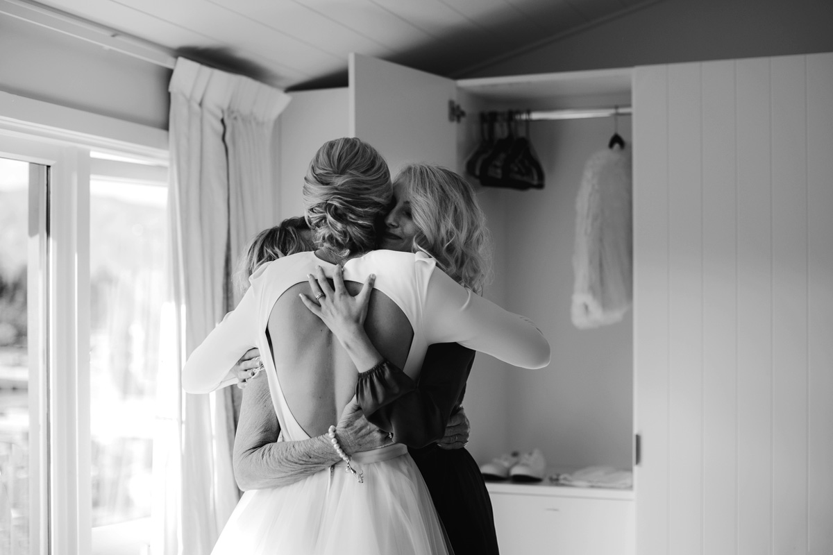 bride, sister and mother hugging