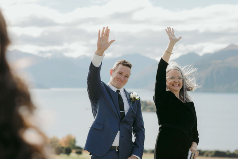 groom and pastor waving to bride