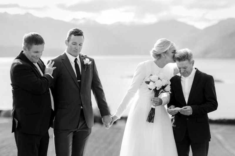 b&w ceremony moment with bride and groom and fathers
