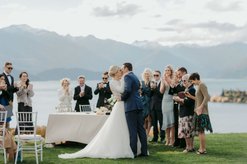 first kiss with guests and mountains and lakes in the background