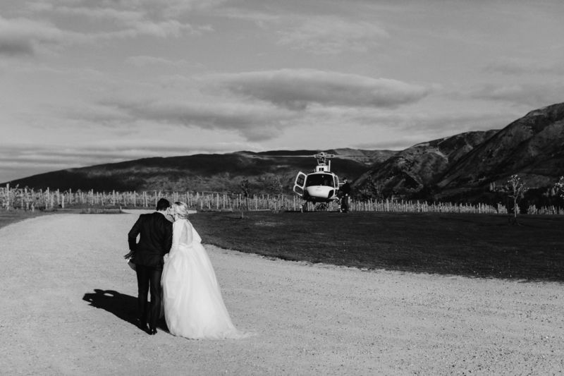 bride and groom stopping for a kiss on way to helicopter