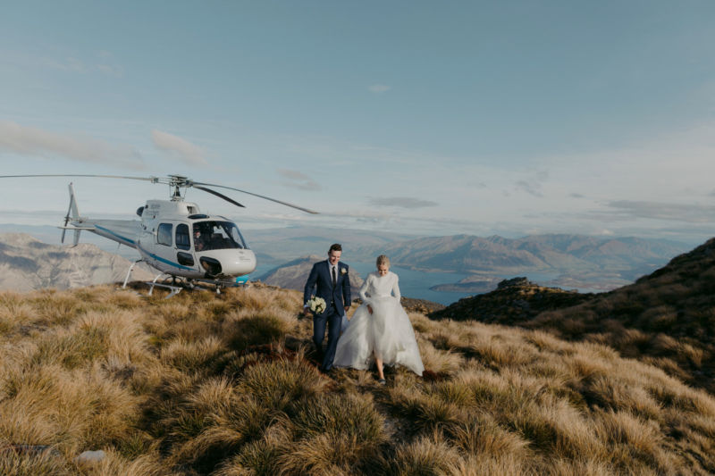bride and groom on mountaintop walking away from heli