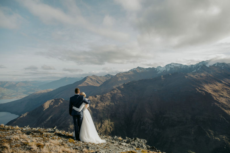 bride and groom on mountaintop hugging from behind