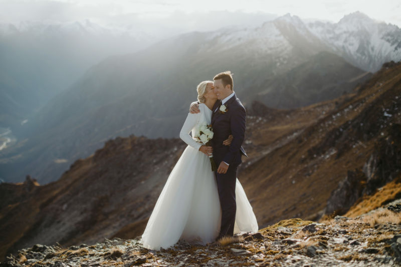 bride and groom on mountaintop hugging from front