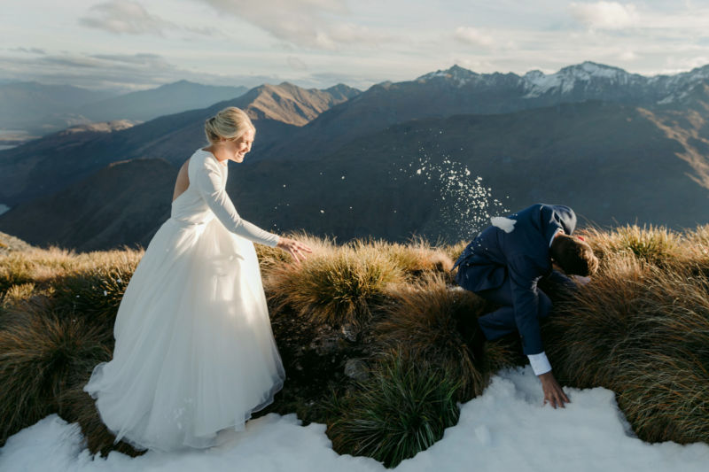 bride and groom on mountaintop bride hitting groom with snowball