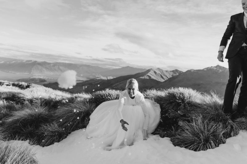 bride and groom on mountaintop bride aiming a snowball at camera