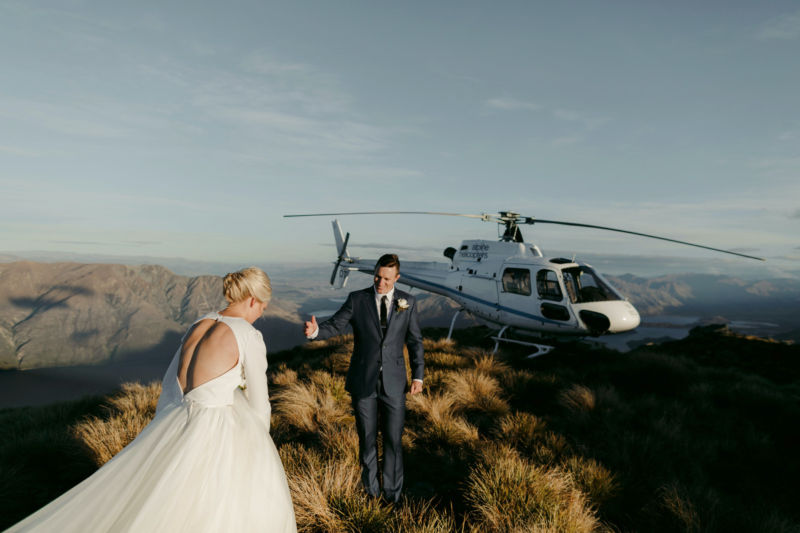 bride and groom heading towards helicopter