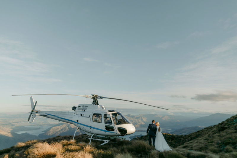 bride and groom pausing to kiss on way to helicopter