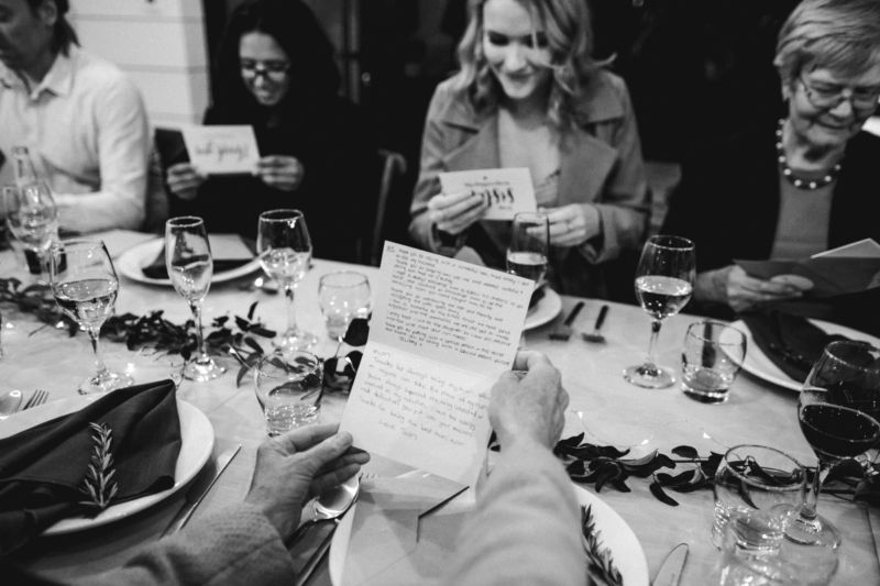 b&w of guests opening personal letters