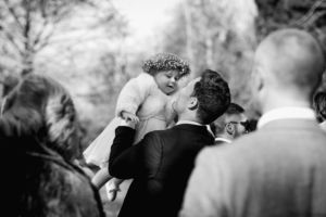 flower girl with flower crown being lifted into the air by groom
