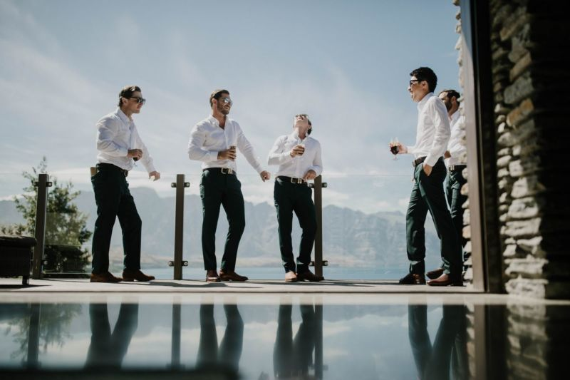 groomsmen drinking with mountain background and reflection on ground