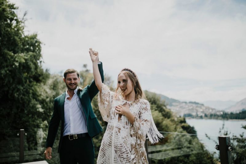 groom raising brides arm in air in celebration
