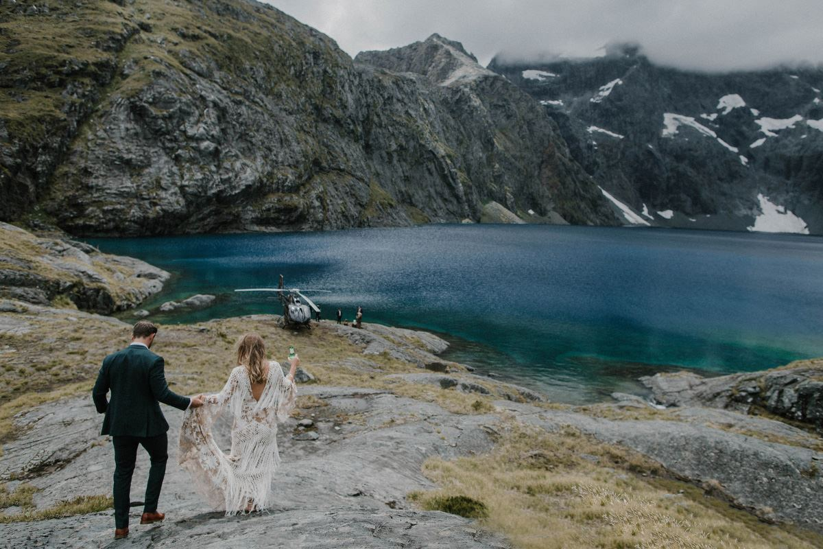 bride and groom walking towards lake with heli in background