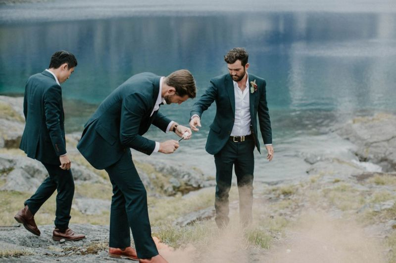 groom and groomsmen lighting smoke bombs